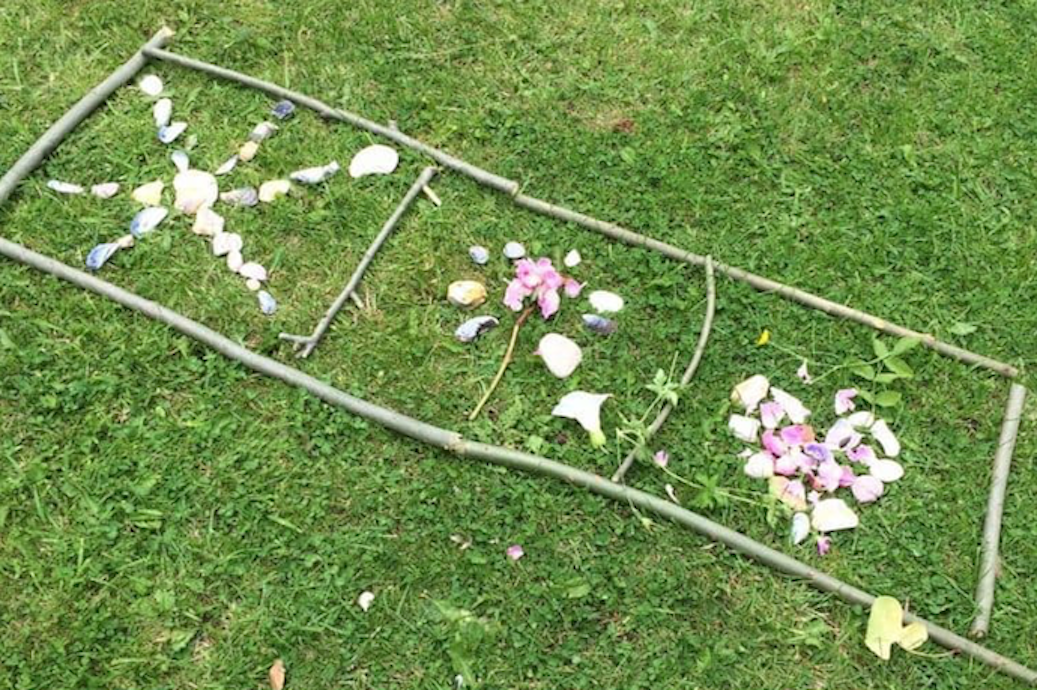 Picture of a nature craft window with sticks, flowers and stones