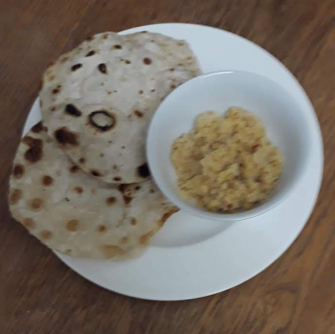 Picture of a couple of flatbreads with a bowl of boiled lentils