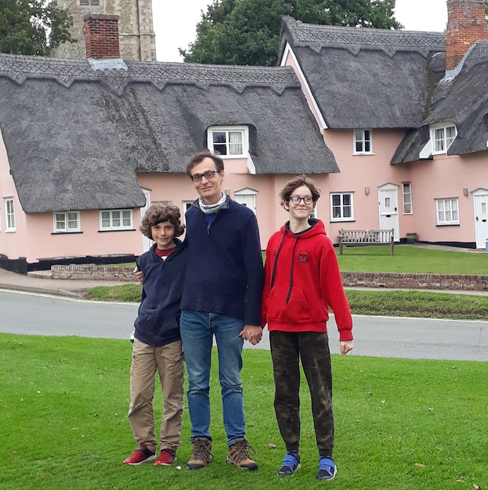 Picture of my husband and kids with thatched cottages