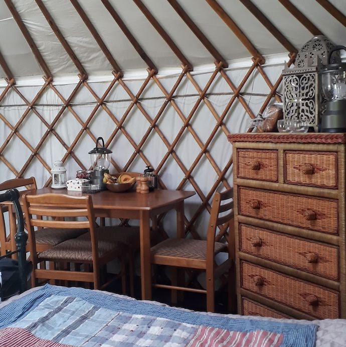 Picture of the inside of our yurt with dining table, chest of drawers and lanterns