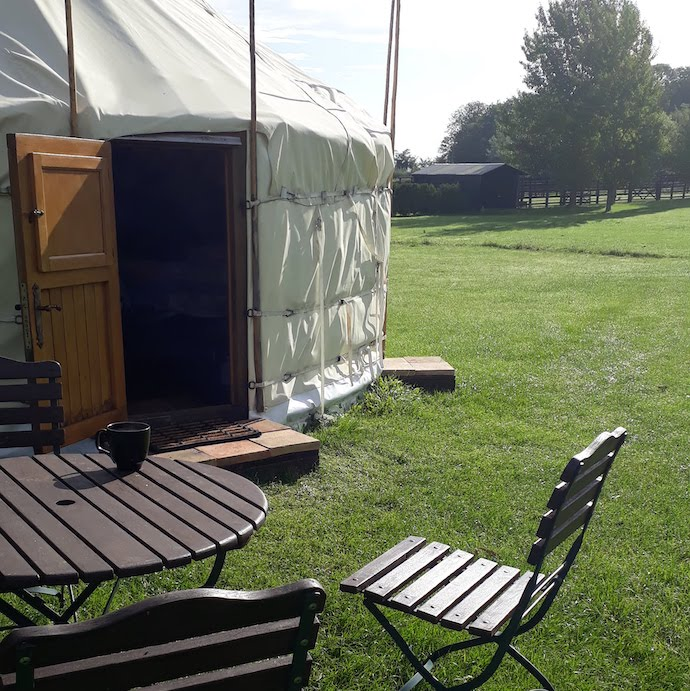 Picture of the door to the yurt with table and chairs outside