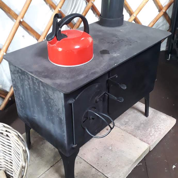 picture of the wood burning stove in our yurt with kettle on top
