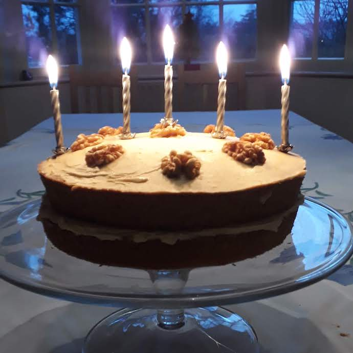 Picture of a coffee and walnut cake with five candles