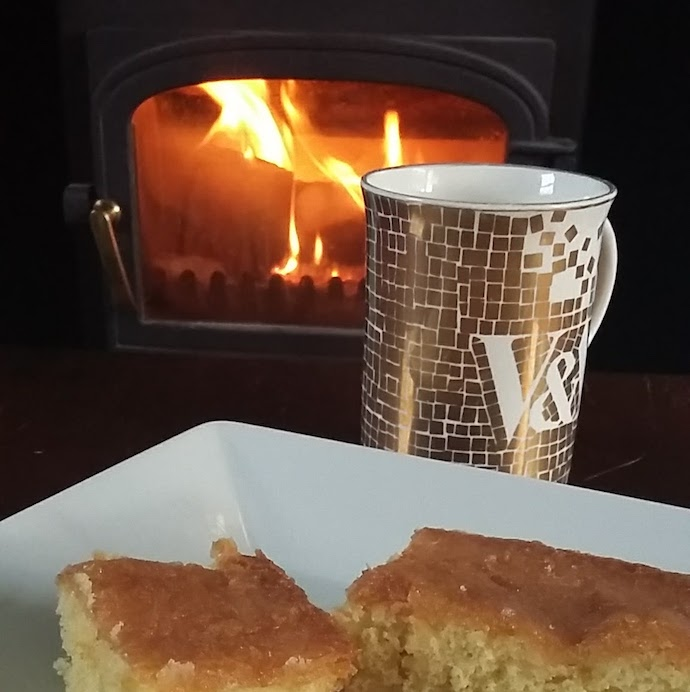 Picture of a tea and cake in front of a woodburner