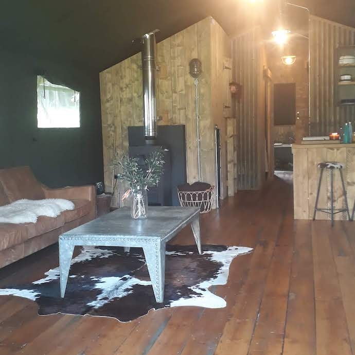 Picture of the inside of our safari tent with sofa and woodburner
